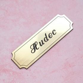 Zlatá nalepovací cedulka se jménem k označení vchodových dveří od bytu